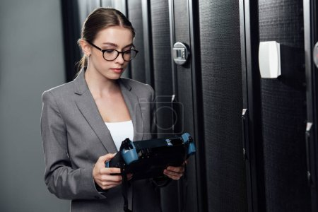 selective focus of businesswoman holding reflectometer in data center