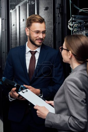 selective focus of handsome businessman holding reflectometer near businesswoman in data center