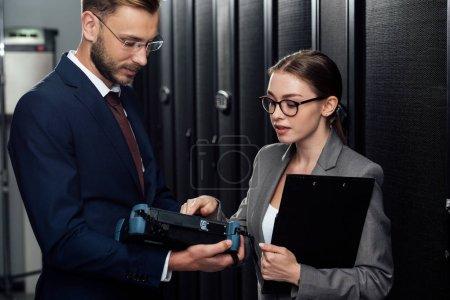 Foto de Empresario guapo en gafas con reflectómetro cerca de empresaria en el centro de datos. - Imagen libre de derechos