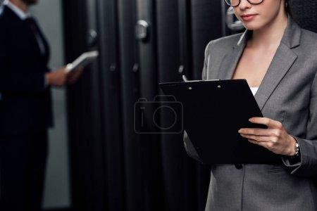 Photo pour Crochet vue d'une femme d'affaires tenant un presse-papiers près d'un homme d'affaires et de porte-serveurs - image libre de droit