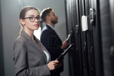 selective focus of attractive businesswoman in glasses holding clipboard near bearded businessman in data canter
