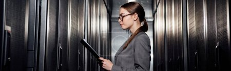 Photo for Panoramic shot of businesswoman in glasses holding clipboard in data center - Royalty Free Image