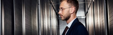 Photo for Panoramic shot of businessman in glasses near server racks in data center - Royalty Free Image