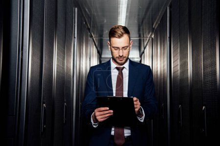 Photo for Handsome businessman in glasses looking at clipboard near server racks - Royalty Free Image