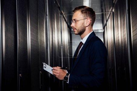 Foto de Vista lateral del hombre de negocios en gafas portadoras de portapeles cerca de las estanterías del servidor. - Imagen libre de derechos