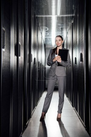 attractive businesswoman holding clipboard while standing in data center