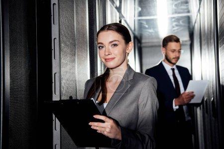 selective focus of cheerful businesswoman holding clipboard near bearded businessman in data canter