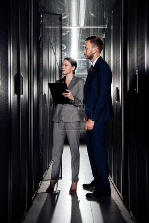 Photo for Attractive businesswoman holding clipboard near bearded businessman in data canter - Royalty Free Image