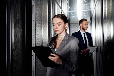 selective focus of attractive businesswoman holding clipboard near businessman in data canter