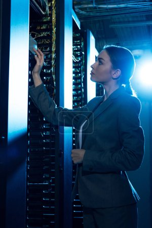 Photo for Attractive businesswoman looking at server rack in data center - Royalty Free Image