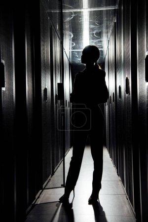 Photo pour Silhouette de femme d'affaires debout dans le centre de données - image libre de droit