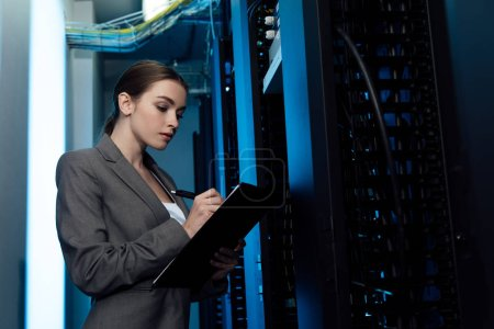 attractive businesswoman writing while holding clipboard in server room