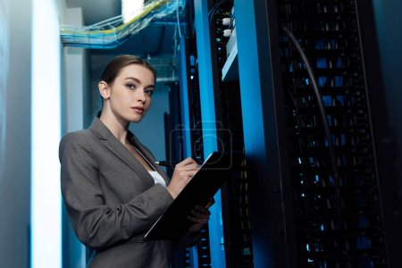 beautiful businesswoman writing while holding clipboard in server room