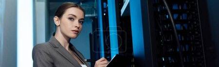 panoramic shot of beautiful businesswoman writing while holding clipboard in server room