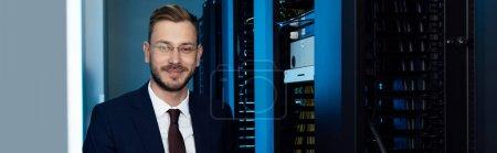 Photo pour Photo panoramique d'un homme d'affaires en lunettes souriant dans un centre de données - image libre de droit