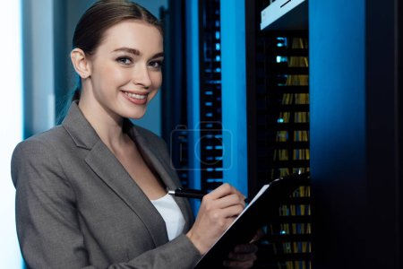 cheerful businesswoman writing while holding clipboard in server room