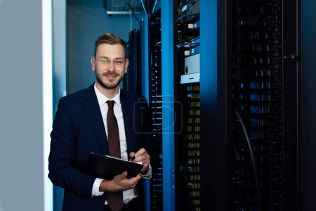 happy businessman in glasses holding clipboard in data center
