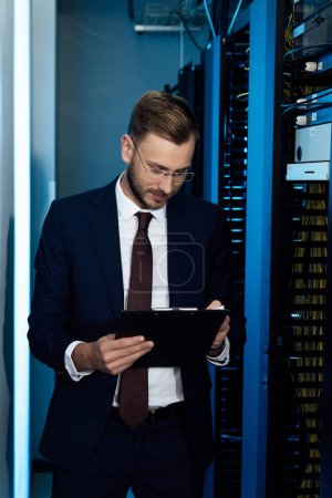 handsome businessman in glasses holding clipboard in data center