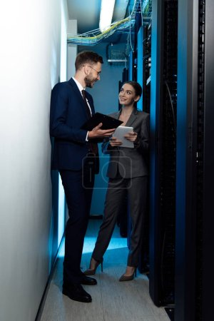 Photo for Cheerful businesswoman and businessman with clipboard in data center - Royalty Free Image