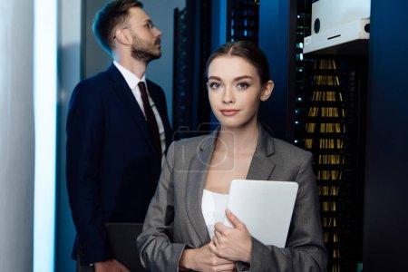Foto de Enfoque selectivo de la atractiva mujer de negocios que tiene tableta digital cerca del hombre de negocios en el centro de datos. - Imagen libre de derechos