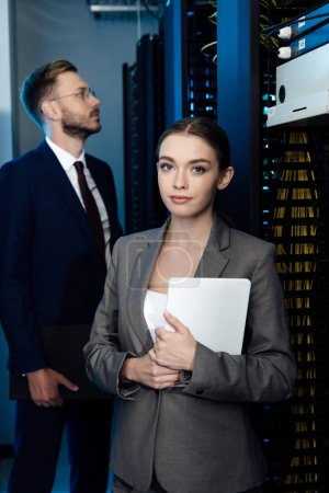 selective focus of attractive businesswoman holding digital tablet near bearded businessman in data center