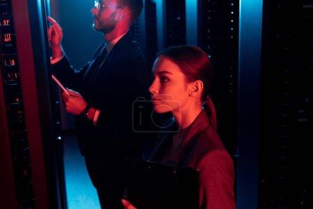 Foto de Enfoque selectivo de una empresaria atractiva cerca de un empresario soportado con tableta digital en el centro de datos. - Imagen libre de derechos