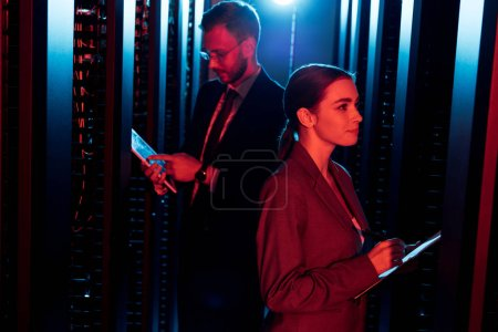 selective focus of attractive businesswoman near businessman with digital tablet in data center