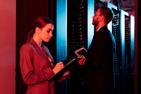 Photo pour Attractive business woman holding clipboard near business man with digital tablet in data center - image libre de droit