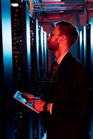 Photo pour Vue latérale d'un homme barbu en lunettes tenant une tablette numérique dans la salle du serveur - image libre de droit