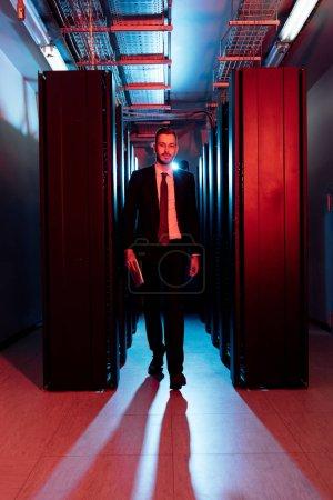 Foto de Empresario portador en gafas con tableta digital y paseando por la sala del servidor. - Imagen libre de derechos