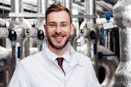 Photo pour Ingénieur gai en lunettes et en manteau blanc regardant la caméra - image libre de droit