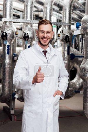 Photo pour Heureux ingénieur en lunettes et manteau blanc debout avec la main dans la poche et en montrant le pouce vers le haut - image libre de droit