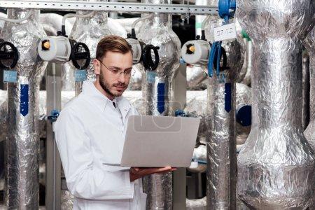 Photo pour Bel ingénieur barbu en manteau blanc tenant un ordinateur portatif - image libre de droit