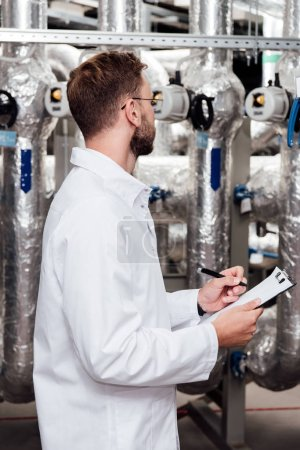 Photo pour Ingénieur barbu en manteau blanc tenant le presse-papiers et le stylo près d'un système à air comprimé - image libre de droit