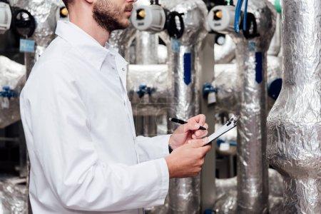 Photo pour Vue recadrée de l'ingénieur barbu en manteau blanc tenant presse-papiers et stylo près du système compressé à l'air - image libre de droit