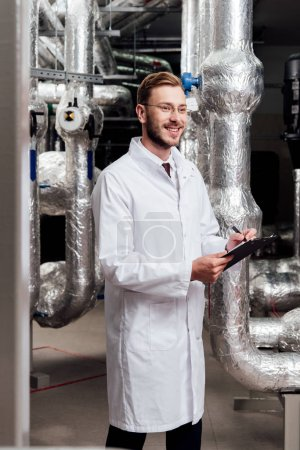 Photo pour Happy engineer in white coat holding pen and clipboard near air compressed system - image libre de droit