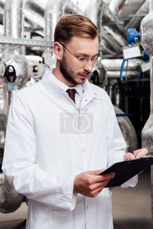 Photo pour Ingénieur barbu en manteau blanc tenant stylo près du presse-papiers et système compressé à l'air - image libre de droit