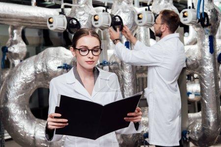 Photo pour Focus sélectif de l'ingénieur attirant en manteau blanc regardant le dossier près du collègue et du système d'air comprimé - image libre de droit