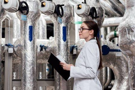 Photo pour Ingénieur attrayant en manteau blanc et lunettes tenant dossier noir près du système compressé à l'air - image libre de droit