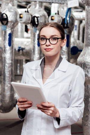 Photo pour Attrayant ingénieur en veste et lunettes blanches tenant une tablette numérique près d'un système à air comprimé - image libre de droit