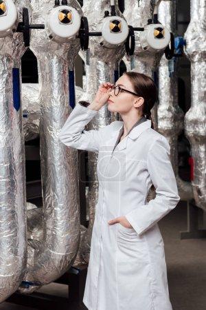 Photo pour Attrayant ingénieur en manteau blanc touchant des lunettes en se tenant debout avec la main dans la poche et en regardant le système à air comprimé - image libre de droit