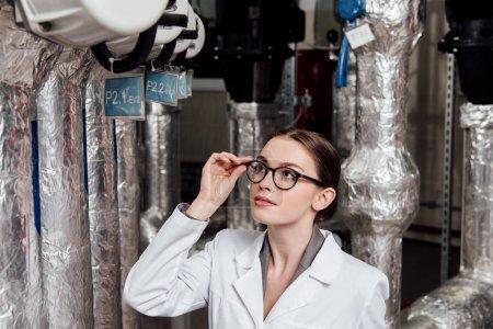 Photo pour Attrayant ingénieur en manteau blanc touchant des lunettes tout en regardant un système à air comprimé - image libre de droit