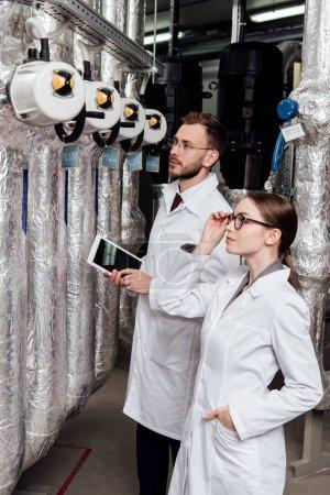Photo pour Bel ingénieur tenant une tablette numérique près d'un collègue regardant un compresseur d'air - image libre de droit