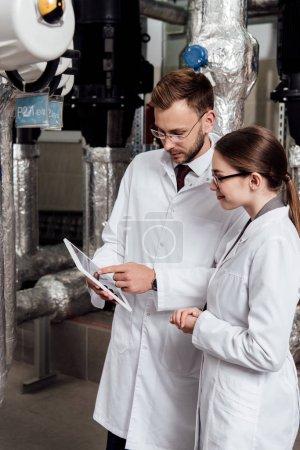 Photo pour Bel ingénieur pointant avec le doigt vers la tablette numérique près de son collègue et du compresseur d'air - image libre de droit
