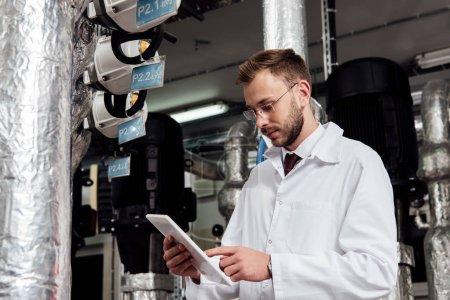 Photo pour L'ingénieur barbu en manteau blanc pointant avec le doigt à la tablette numérique près du système d'alimentation en air - image libre de droit