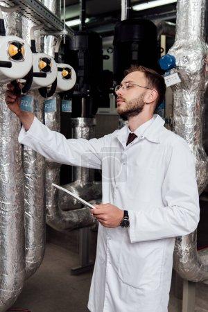 Photo pour Bel ingénieur barbu en manteau blanc tenant tablette numérique près du système d'alimentation en air - image libre de droit