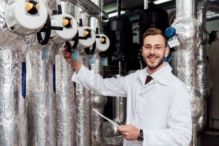 Photo pour Ingénieur gai barbu en manteau blanc tenant une tablette numérique près du système d'alimentation en air - image libre de droit