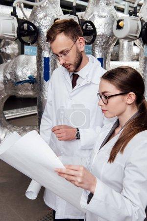 Photo pour Des ingénieurs en manteau blanc examinent un plan détaillé d'un système de compresseur d'air - image libre de droit