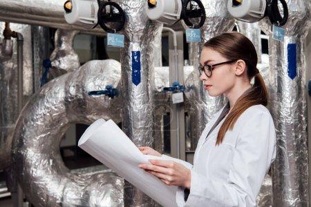 Photo pour Magnifique ingénieur en veste et lunettes blanches regardant un plan près du système d'approvisionnement en air - image libre de droit