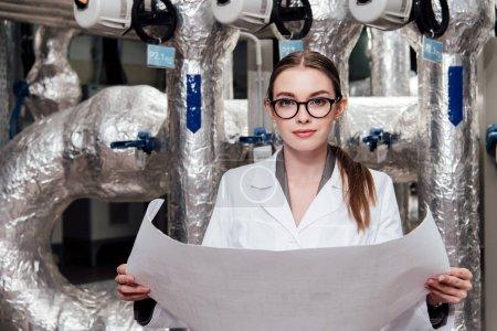 Photo pour Attrayant ingénieur en veste et lunettes blanches tenant un plan près du système d'approvisionnement en air - image libre de droit